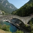 Roman bridge over River Verzasca on Verzasca valley - Stock Photo