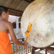 Buddhist monk beats the drum — Stock Photo