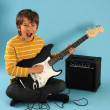 Stock Photo: Young boy playing guitar
