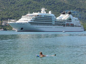 Boy swimming in front of a cruiseship on the bay of Kotor, Monte — Stock Photo
