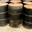Stock Photo: Rows of rusting black drums