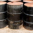 Row of rusting black drums — Stock Photo #32926863