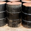 Stock Photo: Row of rusting black drums
