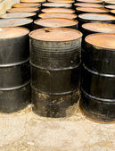 Rows of rusting black drums — Stock Photo
