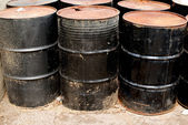 Row of rusting black drums — Stock Photo