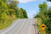 Colina na estrada com o sinal de lombada — Fotografia Stock