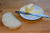Bread with butter on plate — Stock Photo