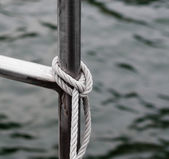 Rope tied to metal railing near water. — Stock Photo