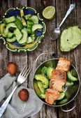 Grilled salmon with avocado and cucumber salad — Photo