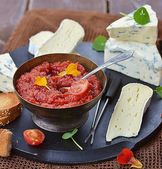 Cheese plate with tomato chutney — Stock Photo