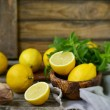 Juicy and ripe organic lemons in a and fresh mint on a wooden background — Stock Photo #50101973