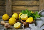 Juicy and ripe organic lemons in a and fresh mint on a wooden background — Stock Photo