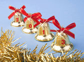 Christmas golden bells and red ribbon — Stock Photo