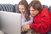 Brother and sister playing games on laptop — Stock Photo