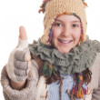Beautiful young girl in warm winter clothes showing thumb up — Stock Photo #19489241