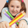 Smiling girl holding color pencils — Stock Photo