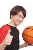Portrait of a handsome smiling basketball player showing thumb u — Stockfoto
