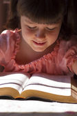 Beautiful little girl reading bible — Stock Photo