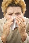 Senior woman sneezing — Stock Photo