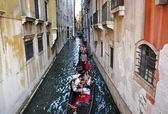 VENICE-JUNE 15: Gondolier runs the gondola with group of tourists on the Venetian canal on June 15, 2012 in Venice, Italy. — Stock Photo