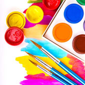 Art studio paints on the white with paintings — Stock Photo