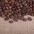 Coffee beans on burlap background — Stock Photo