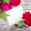 Roses with card on wooden boards — Stock Photo #30177427