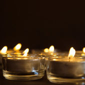 Group of burning candles on black background — Stock Photo