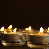 Skupina hořící svíčky na černém pozadí — Stock fotografie
