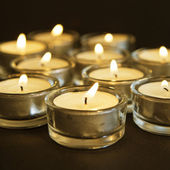 Group of burning candles on black background. — Stock Photo
