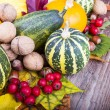 Assorted pumpkins with autumn leaves on wooden table — Stock Photo