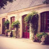 Hus exteriör omgiven av blommor och växter — Stockfoto
