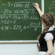 Stock Photo: Schoolgirl at the blackboard writes