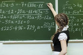 Schoolgirl at the blackboard writes — 图库照片