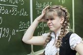Schoolgirl at the blackboard writes — Foto de Stock