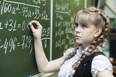 Schoolgirl at the blackboard writes — Stock Photo