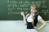 Schoolgirl at the blackboard writes — Stok fotoğraf