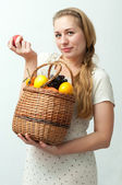 Blonde with a basket of fruit — Stock Photo