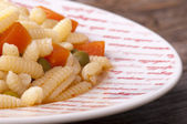 Sardinian gnocchi with peas and carrots in broth — Stock Photo
