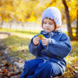 Little curly girl sits in autumn park — Stock Photo