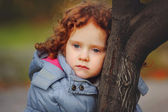 Little curly girl on a tree in park — Stock Photo