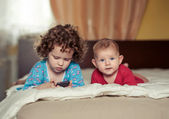 Two kids lie on a bed — Stock Photo