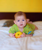 The beautiful baby holding yellow apple — Stock Photo