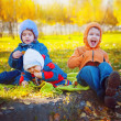 Three smiling young friends sitting on grass — Stock Photo