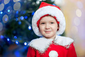 Santa boy smiles near a fir-tree — Stock Photo