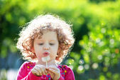 Beautiful little curly girl blowing dandelion — Stock Photo