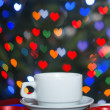 A cup of coffee on the abstract background bokeh hearts — Stok fotoğraf