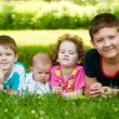 Stock Photo: Children lie on the green grass in the park