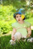 Portrait of a beautiful little girl in a summer park on a green — Stock Photo