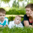 Happy children lie on the green grass in the park — Stock Photo #18488467